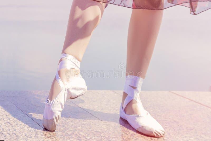 在他们的脚舞蹈家女孩跳舞的芭蕾舞鞋穿上鞋子的 免版税库存图片
