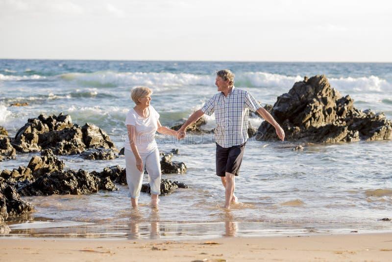 在他们的60s或70s的可爱的资深成熟夫妇退休了走愉快和轻松在海滩在浪漫一起变老的海岸 库存照片