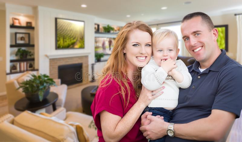 在他们美丽的客厅里面的年轻军事家庭 免版税库存照片