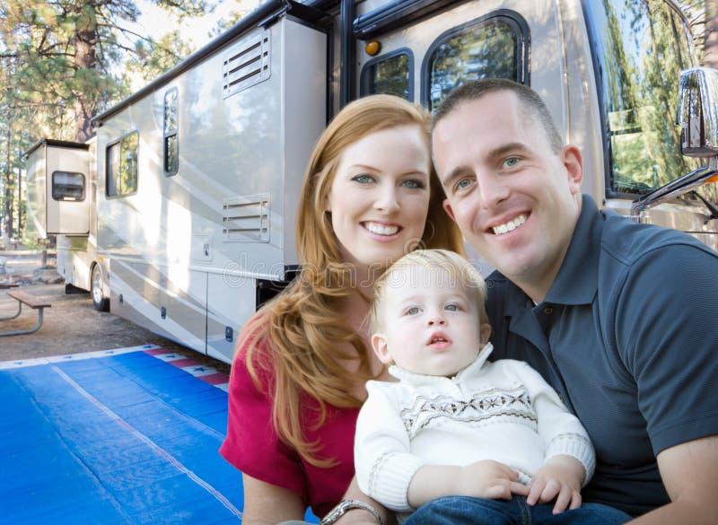 在他们美丽的RV前面的愉快的年轻军事家庭在Th 库存照片