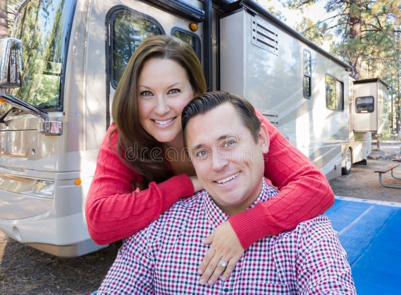 在他们美丽的RV前面的愉快的白种人夫妇在阵营 库存图片