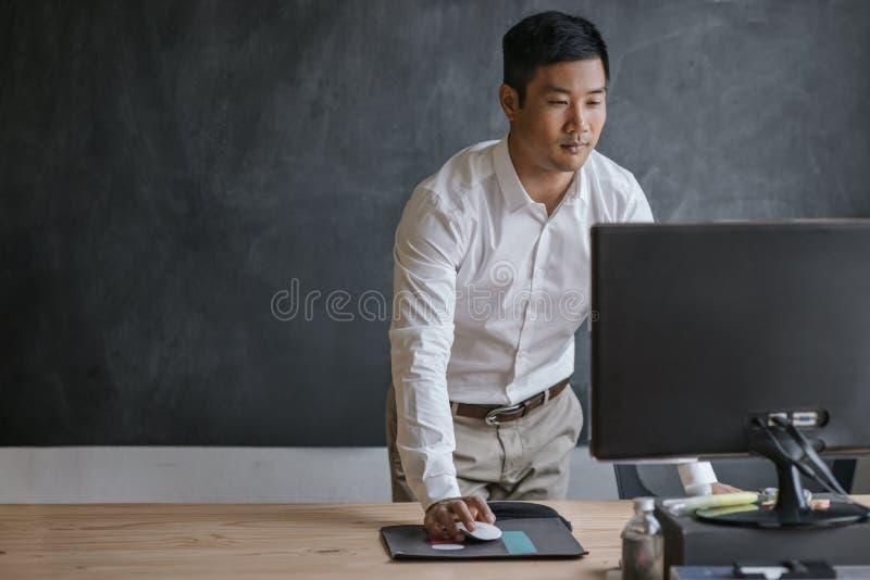 在他的书桌工作的亚洲商人身分在计算机上 免版税库存照片