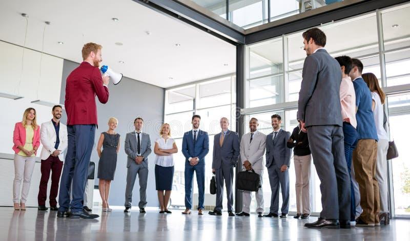 在他的企业队前面的专业上司在扩音机的身分和谈话 免版税库存照片