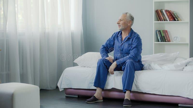 在他的坐长沙发和微笑在早晨体操以后的50s的喜悦的男性 库存照片