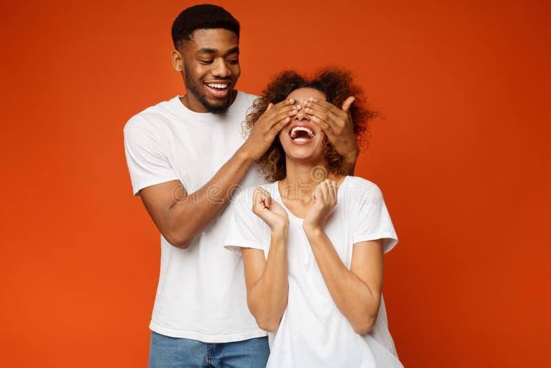 在他的女朋友后的黑人身分和闭上她的眼睛 库存照片