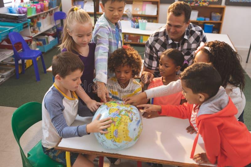 在他的学校孩子的教师陈列地球地球 库存图片