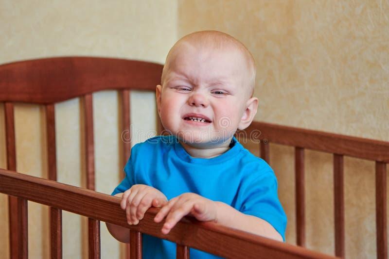 在他的小儿床做鬼脸一个滑稽的男孩的画象 库存照片