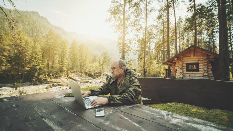 在他的有膝上型计算机的避暑别墅附近供以人员企业家 免版税库存图片