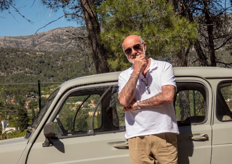 在他的汽车附近的更老的微笑的人在好日子 图库摄影