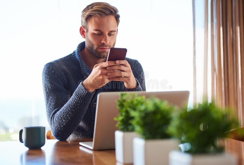 在他的电话的年轻白种人成人人传讯在家 免版税库存图片