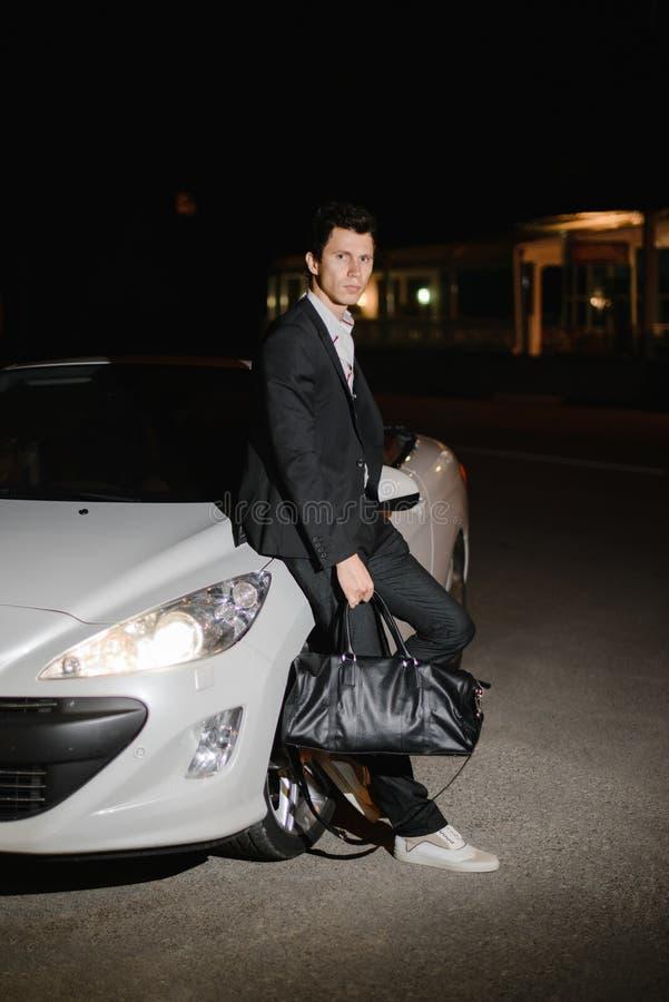 在他的白色敞蓬车旁边的时髦的年轻人身分 夜生活 在衣服的商人在豪华汽车 免版税库存照片