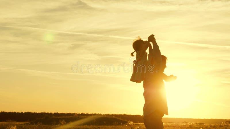 在他的肩膀的爸爸跳舞与他的太阳的女儿 父亲旅行与他的肩膀的婴孩在日落光芒  A 免版税库存图片