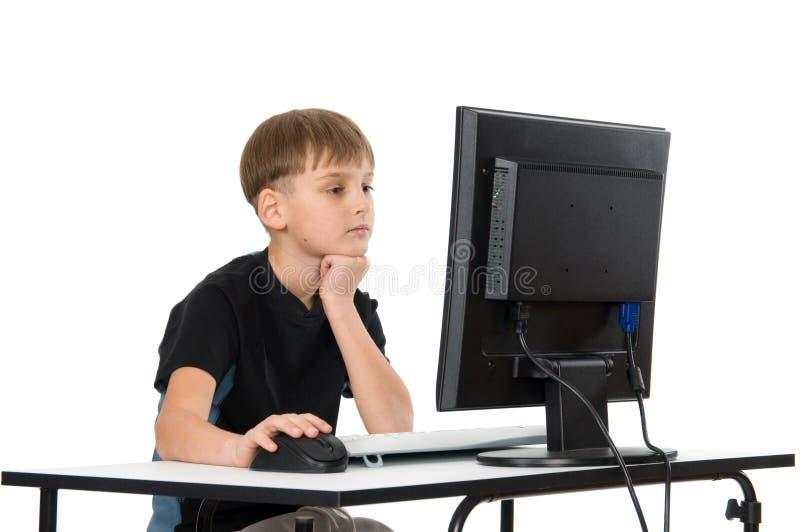 在他的计算机上的男孩 免版税库存图片