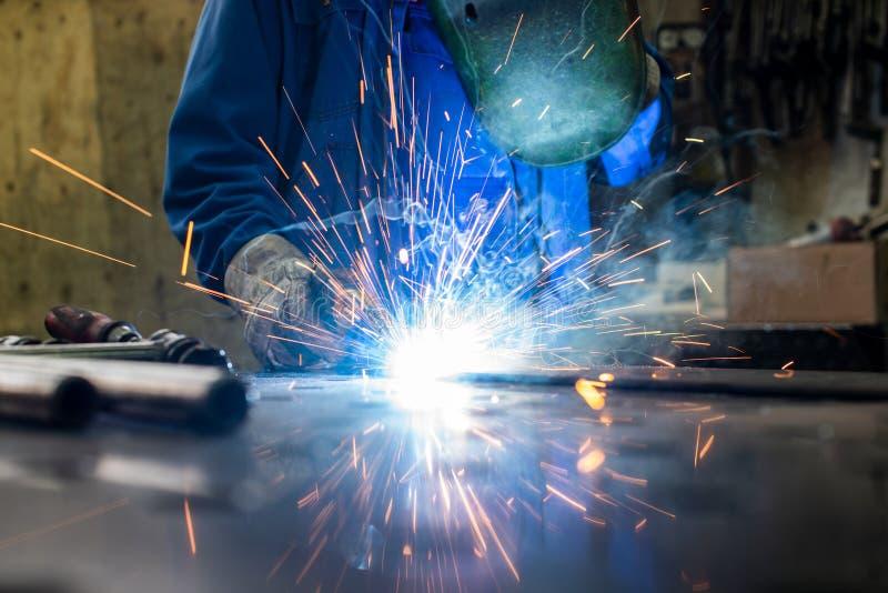 在他的车间焊接金属的焊工 库存图片