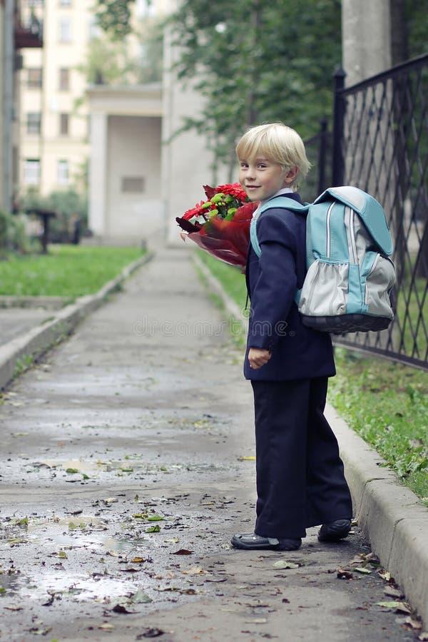 在他的途中的男小学生对学校 去头等的男孩在他的道路的学校 孩子和教育在城市 免版税库存照片