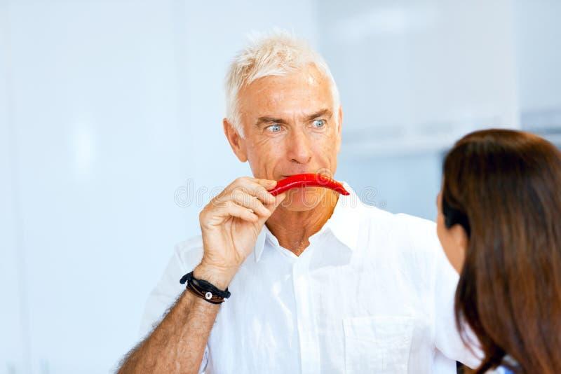 在他的面孔旁边供以人员拿着一个红辣椒 库存图片