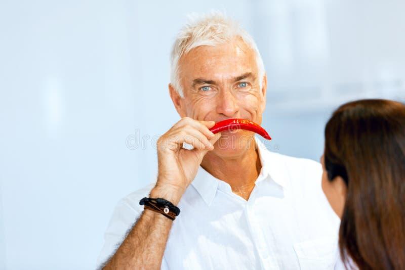 在他的面孔旁边供以人员拿着一个红辣椒 免版税库存照片