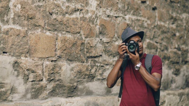 在他的dslr照相机的非裔美国人的愉快的旅游采取的照片 站立在著名大厦附近的年轻人在欧洲 库存图片