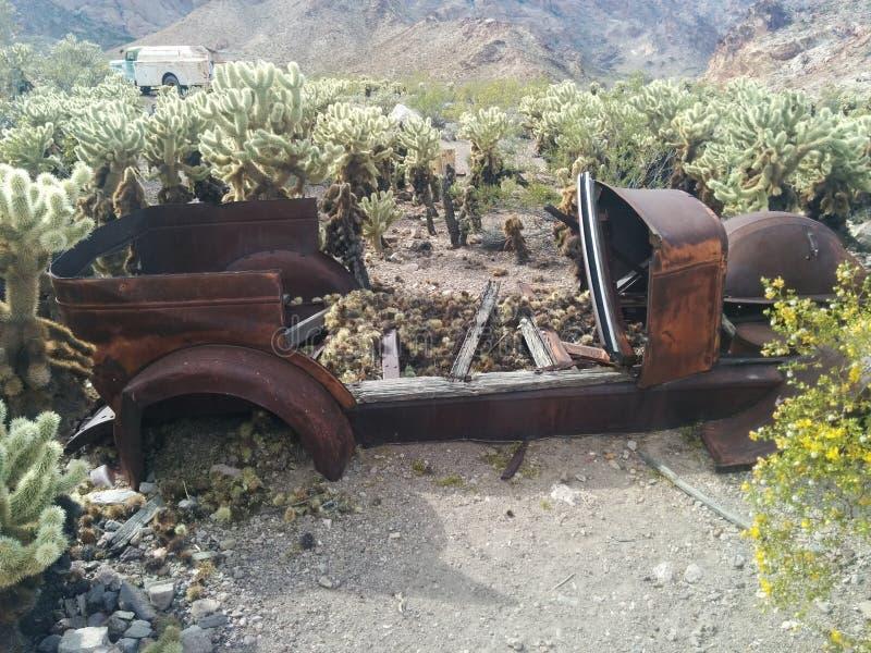 在仙人掌补丁的老,生锈的葡萄酒汽车 图库摄影
