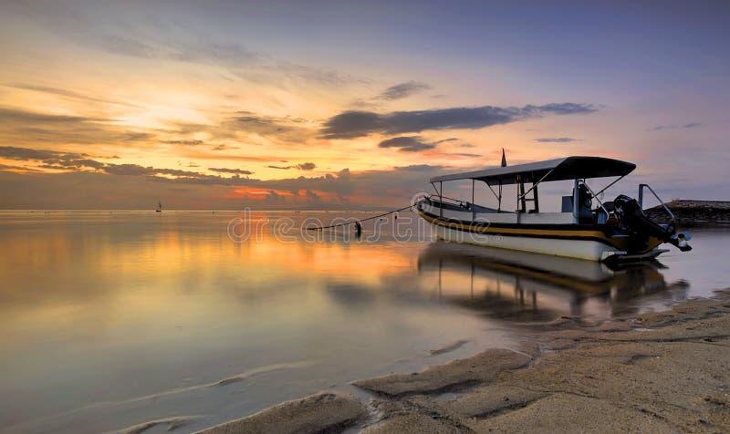 在令人惊讶的日落期间的客船在巴厘岛海滩,印度尼西亚 免版税图库摄影