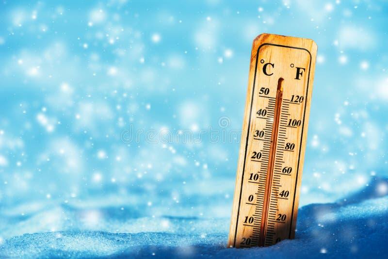 在以下冷的温度零在雪的温度计 免版税库存照片