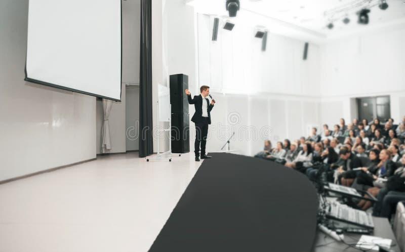 在企业大会和介绍的报告人 在会议室的观众 库存图片