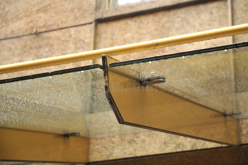 在企业大厦的玻璃门廊在下雨天 免版税图库摄影