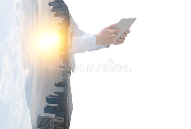 在企业概念的两次曝光,拿着片剂有与伪造品f的风景、建筑或者都市风景背景的商人 图库摄影