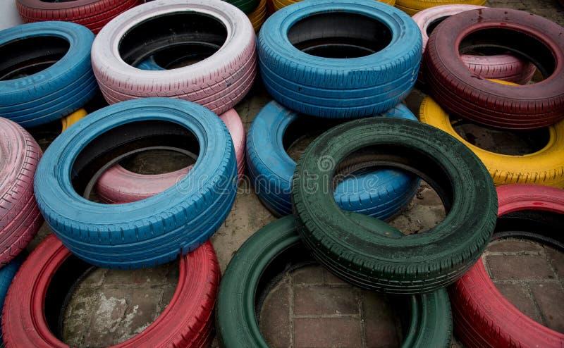 在企业街道的五颜六色的老轮胎装饰 库存照片