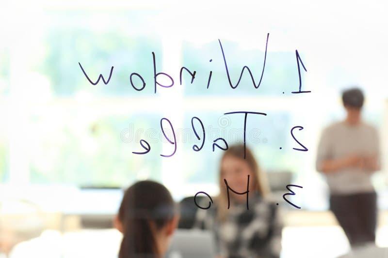 在企业队的看法在见面期间在办公室通过有文字的透明委员会 库存照片