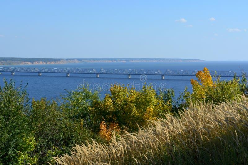 在伏尔加河的桥梁在晴朗的9月天 从上面的看法与树和谷物在前景 免版税库存照片