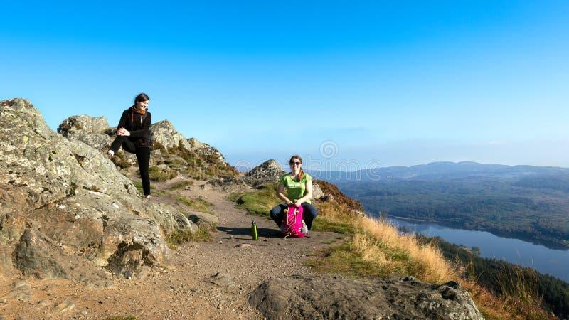 在休假和享受谷视图的山顶部的女性远足者 免版税库存照片