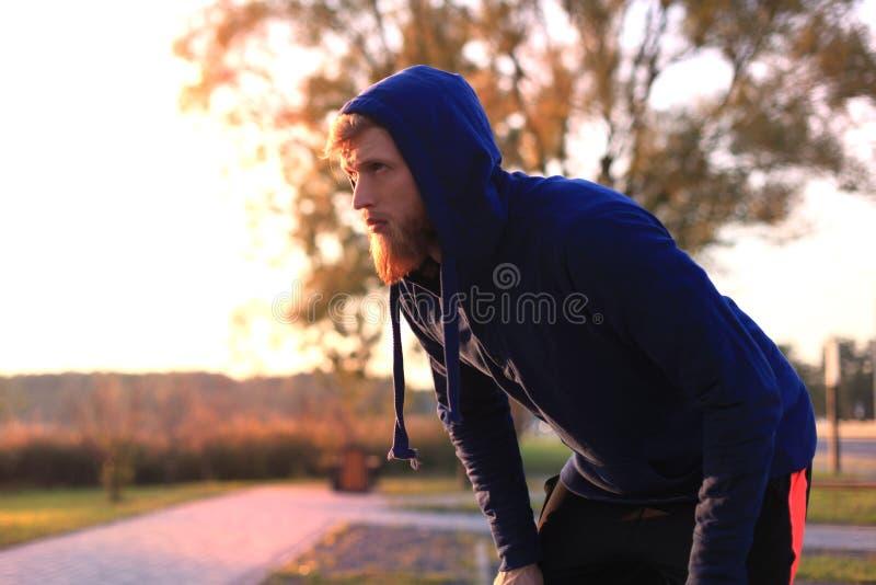 在休息在凹凸部以后的奔跑以后的英俊的年轻人在公园在日落或日出 库存图片