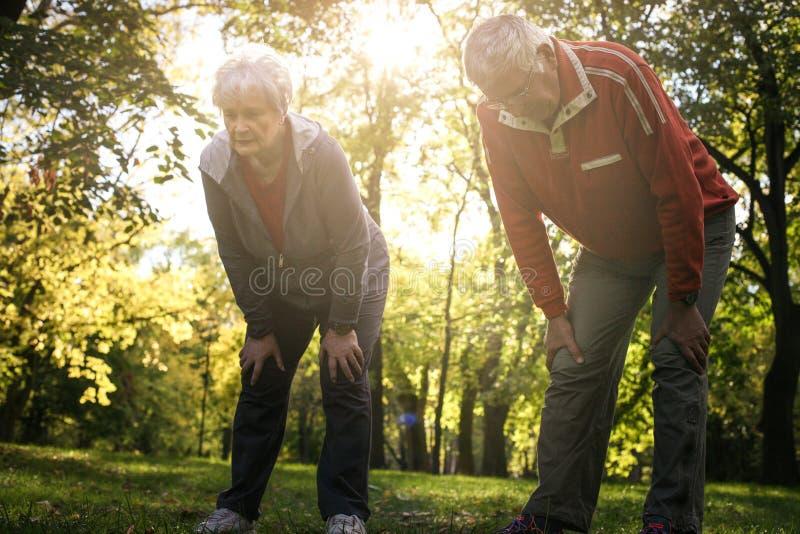 在休息在锻炼以后的体育衣物的疲乏的资深夫妇 免版税库存照片