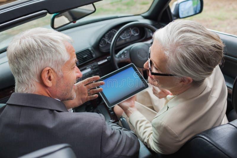 在优等的汽车的片剂的微笑的成熟伙伴 免版税库存图片