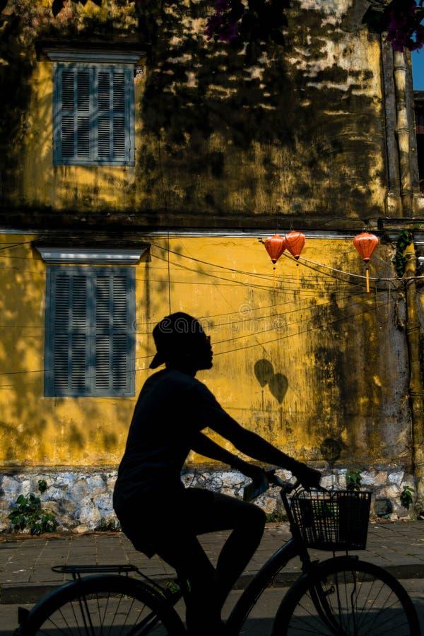 在会安市骑自行车镇的游人 免版税库存照片