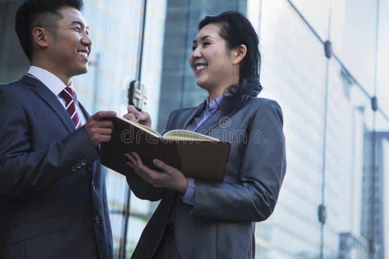 在会议和文字之外的两个微笑的商人在个人组织者 免版税库存照片