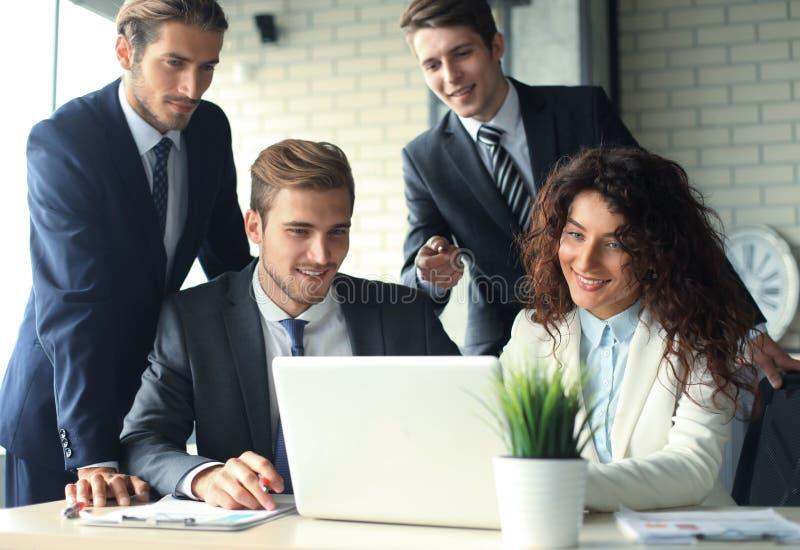 在会议在内部现代明亮的办公室和工作的起始的企业队在膝上型计算机 库存图片