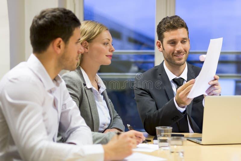 在会议室的三个商人 免版税库存照片