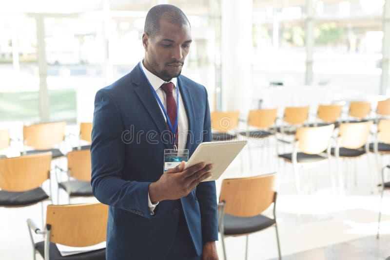 在会议室观看的片剂的非裔美国人的商人身分 免版税库存图片