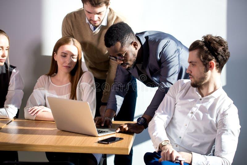 在会议的企业队在办公室激发灵感、工作在膝上型计算机和计算机 免版税库存照片