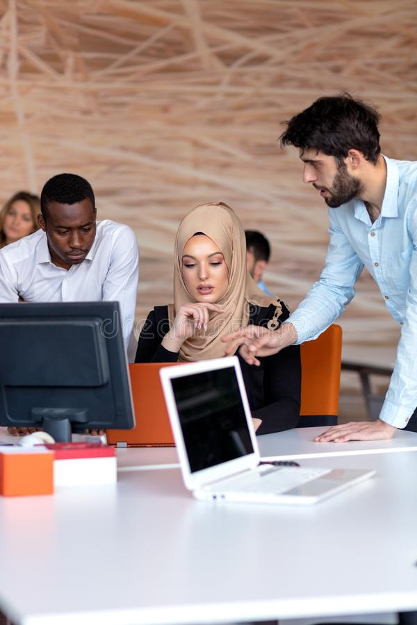 在会议的起始的企业队在现代明亮的办公室内部激发灵感、工作在膝上型计算机和片剂计算机 图库摄影