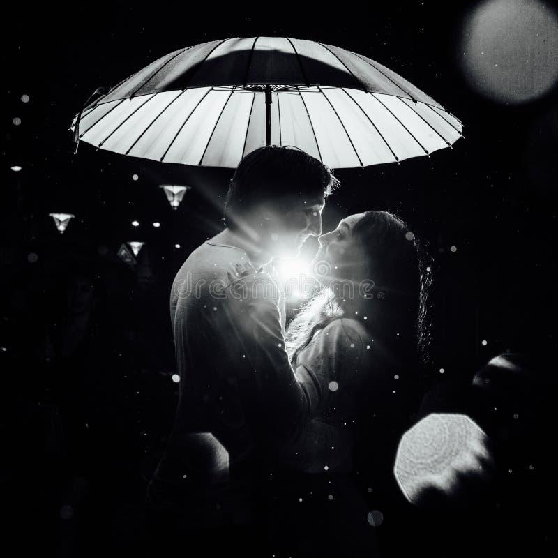 在伞亲吻下的年轻夫妇在城市街道上的晚上 图库摄影