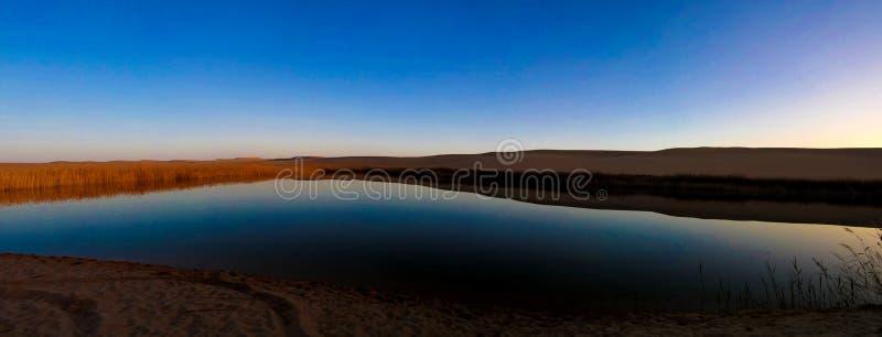 在伟大的沙子海和湖的全景风景在日落的Siwa绿洲附近在埃及 免版税库存照片