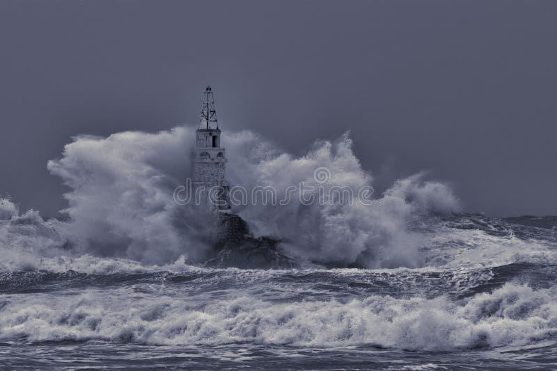 在伟大的风雨如磐的波浪中间的老灯塔 反对岩石的碰撞的大海波浪飞溅并且喷洒 巨大的风雨如磐的海波浪 免版税图库摄影