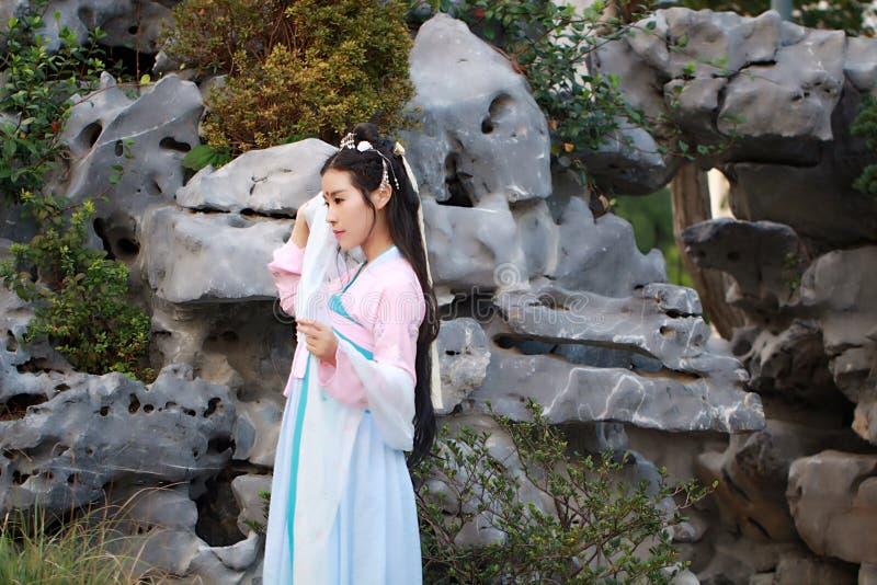 在传统古老戏曲服装的汉语经典秀丽支持假山庭园 库存照片