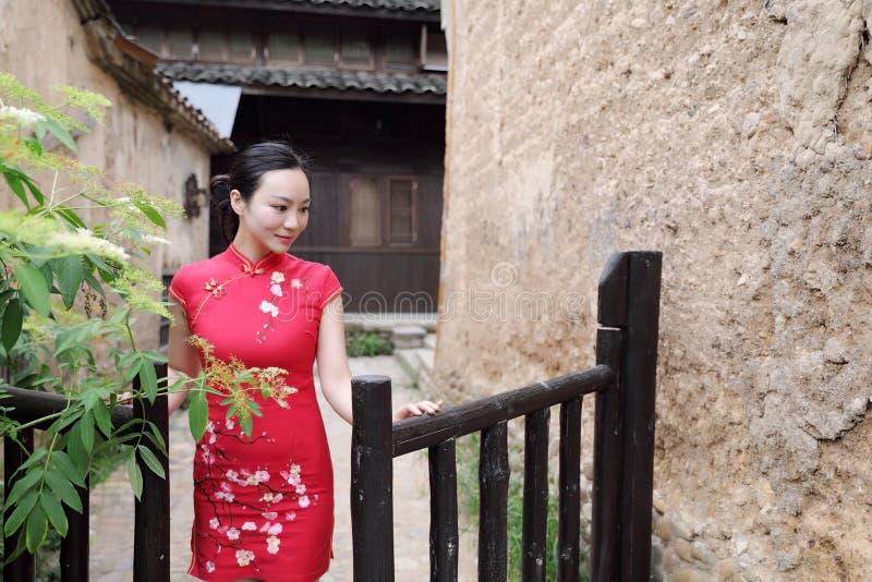 在传统古老礼服服装红色cheongsam的亚洲东部东方中国妇女秀丽在古镇庭院篱芭 库存图片