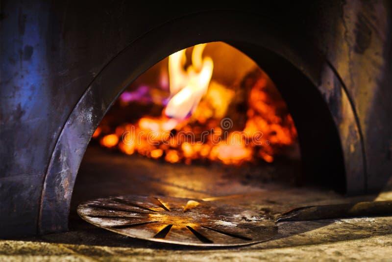 在传统意大利砖比萨烤箱前面的铁锹 图库摄影