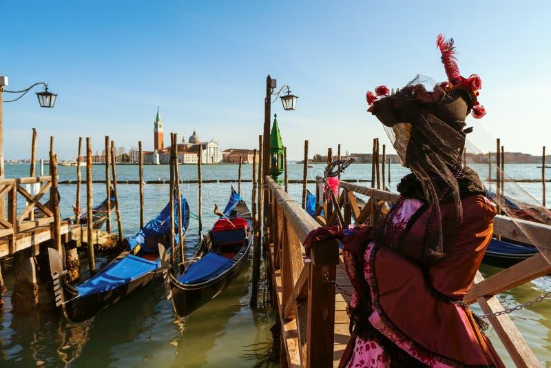 在传统服装打扮的狂欢节参加者在大运河附近在威尼斯 免版税库存图片