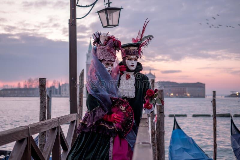 在传统服装的浪漫在日出的夫妇和面具,站立与回到大运河和圣乔治,威尼斯,意大利 免版税库存图片